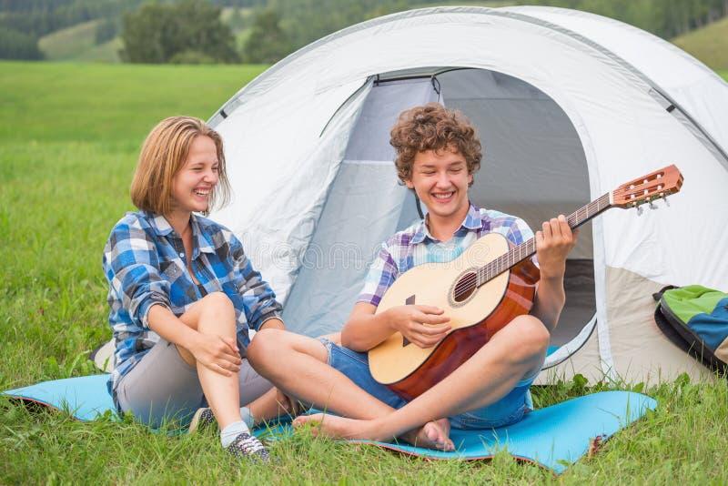 十几岁的男孩和女孩在弹吉他的帐篷附近户外 库存图片