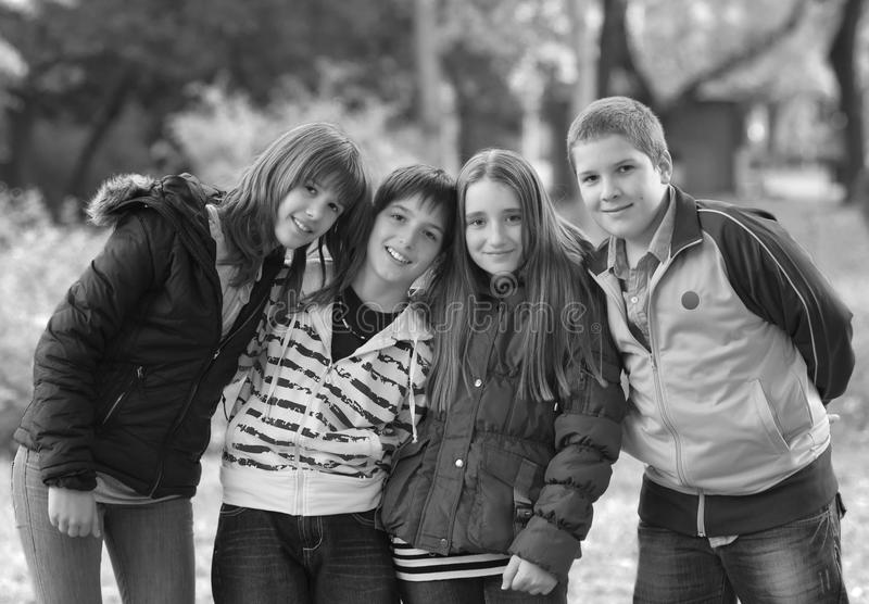 十几岁的男孩和女孩获得乐趣在公园在春天 库存图片