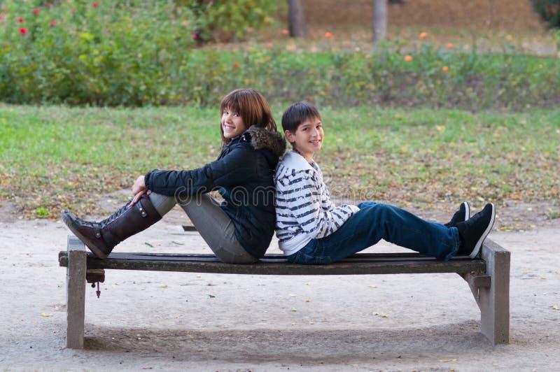 十几岁的男孩和女孩获得乐趣在美好的秋天的公园 库存照片