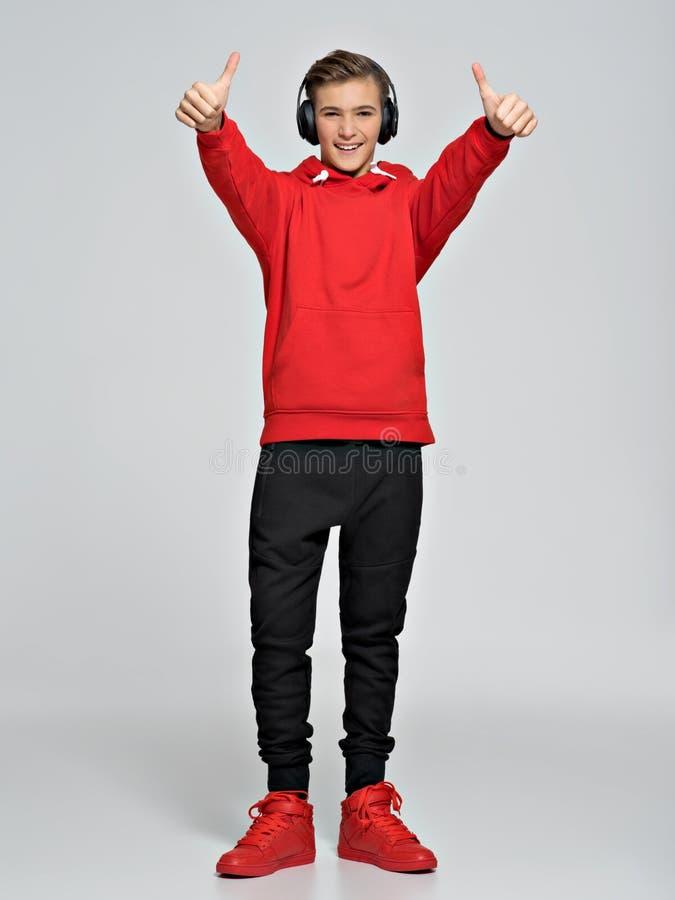 十几岁的男孩在一红色有冠乌鸦和街道运动鞋穿戴了 免版税图库摄影