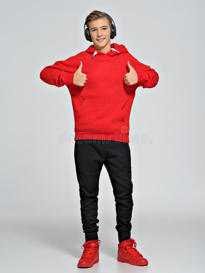 十几岁的男孩在一红色有冠乌鸦和街道运动鞋穿戴了 免版税库存图片