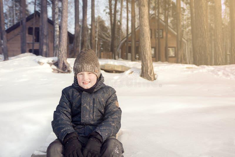 十几岁的男孩坐白雪 免版税图库摄影