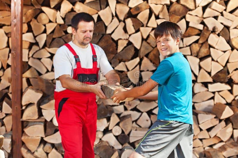 十几岁的男孩帮助的父亲堆积木柴 免版税库存照片