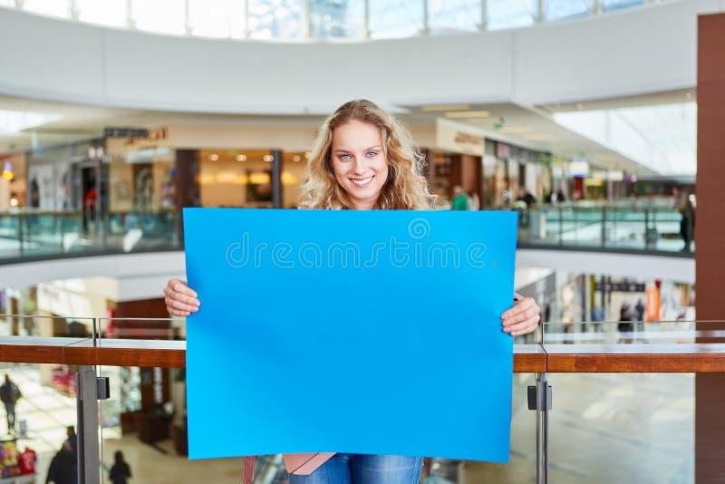 十几岁的男孩拿着一块蓝色空白的牌 库存图片
