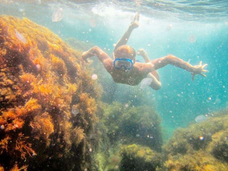 十几岁的男孩游泳在水下在海 图库摄影