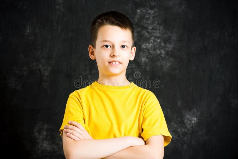 十几岁的男孩画象反对黑暗的背景的 库存图片