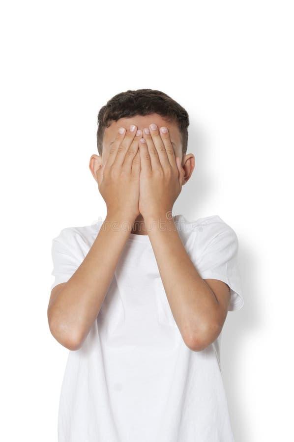 十几岁的男孩皮他的面孔用他的手 库存图片