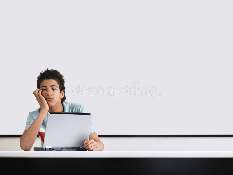 十几岁的男孩看在whiteboard前面乏味在教室 库存照片