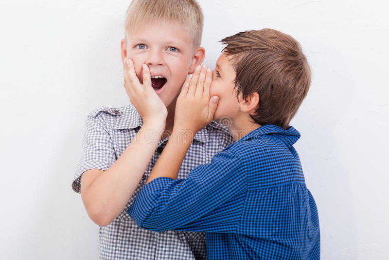 十几岁的男孩耳语在耳朵秘密 免版税库存图片