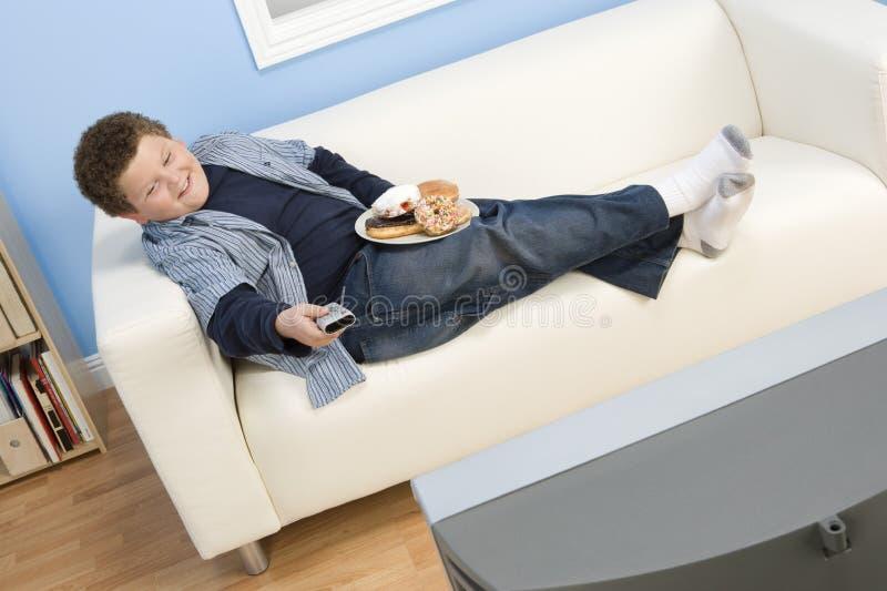 十几岁的男孩观看的电视 免版税库存图片