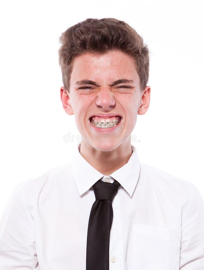 十几岁的男孩鬼脸有大括号的。 查出在空白背景 库存图片