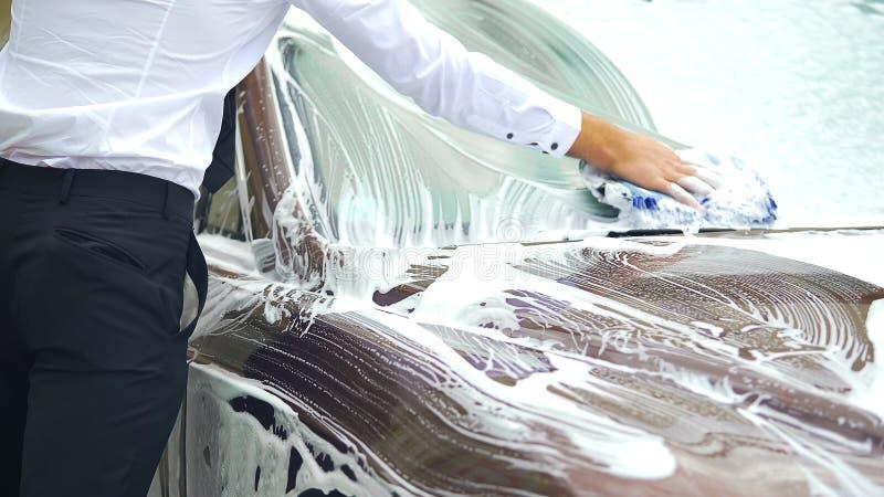 十分地洗涤他的豪华汽车的挡风玻璃一丝不苟的司机,洗车 免版税库存照片