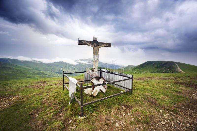十字架和云彩在山在日出 免版税库存照片