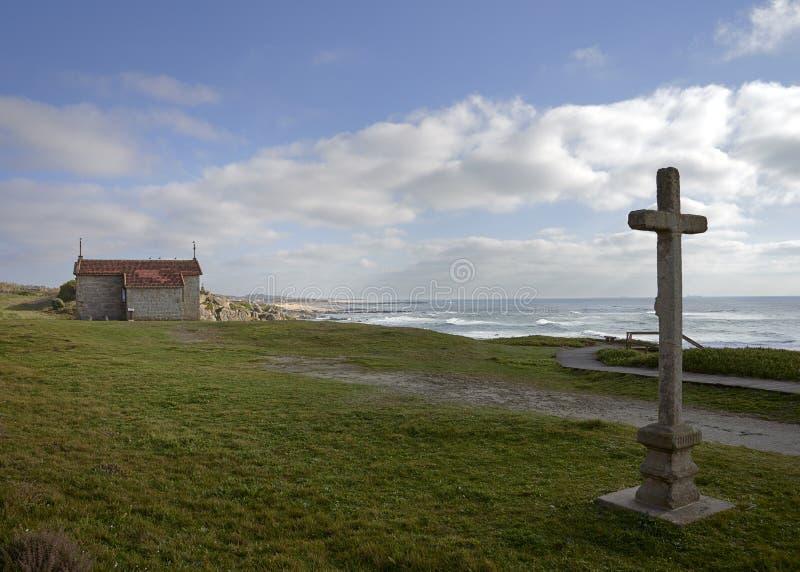 十字架和教会在卡斯特罗de SA£oo Paio,俯视海滩 免版税图库摄影