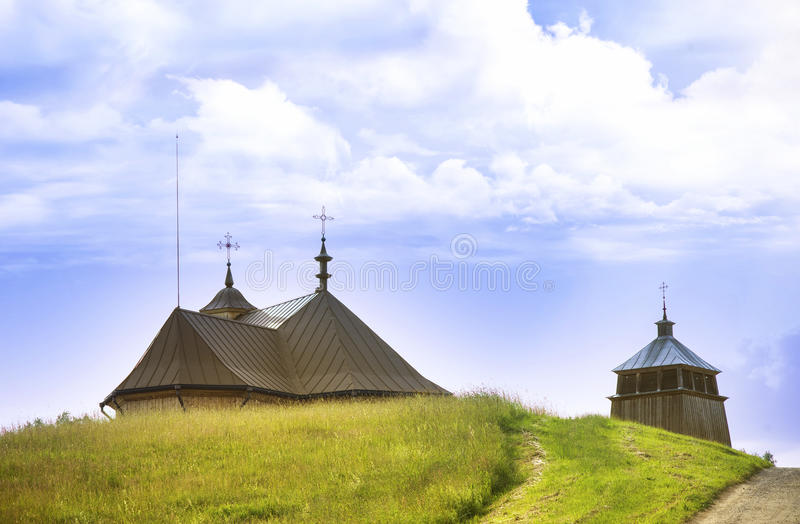 十字架和教会屋顶安心在小山后的 库存图片
