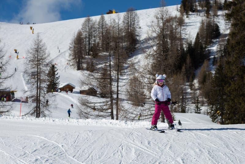 十年的矮小的滑雪者有乐趣滑雪在意大利白云岩阿尔卑斯山 免版税库存图片