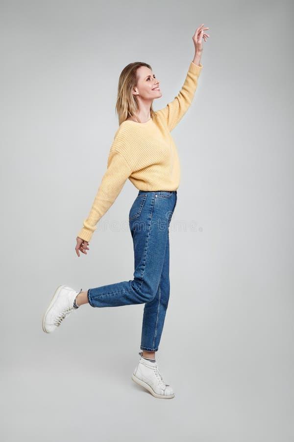 千福年逗人喜爱的俏丽的女孩全长身体尺寸视图照片有唬弄被隔绝的感觉的自由举行手的步行激动 免版税图库摄影