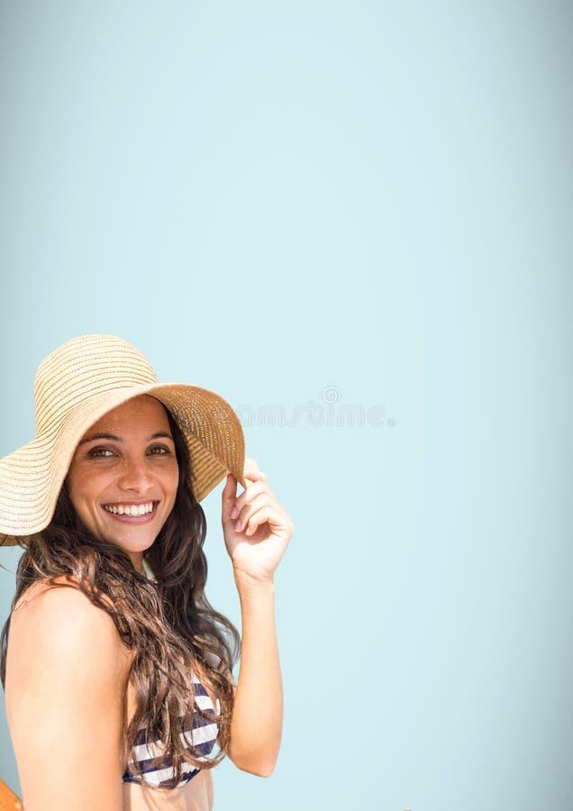 千福年的妇女太阳帽子和比基尼泳装反对浅兰的背景 免版税库存照片