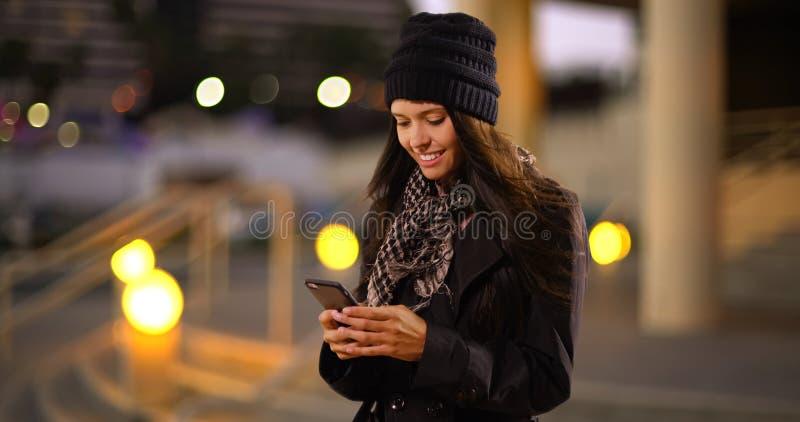 千福年的白女孩在城市发短信给她的朋友 免版税库存照片
