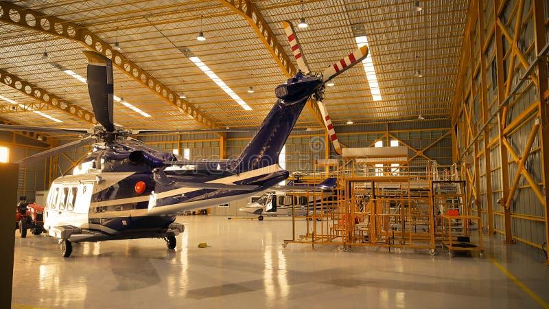 直升机停车处在飞机棚和为飞行做准备由流动代课教师组 免版税库存照片