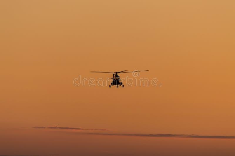 直升机剪影有日落天空的 库存图片
