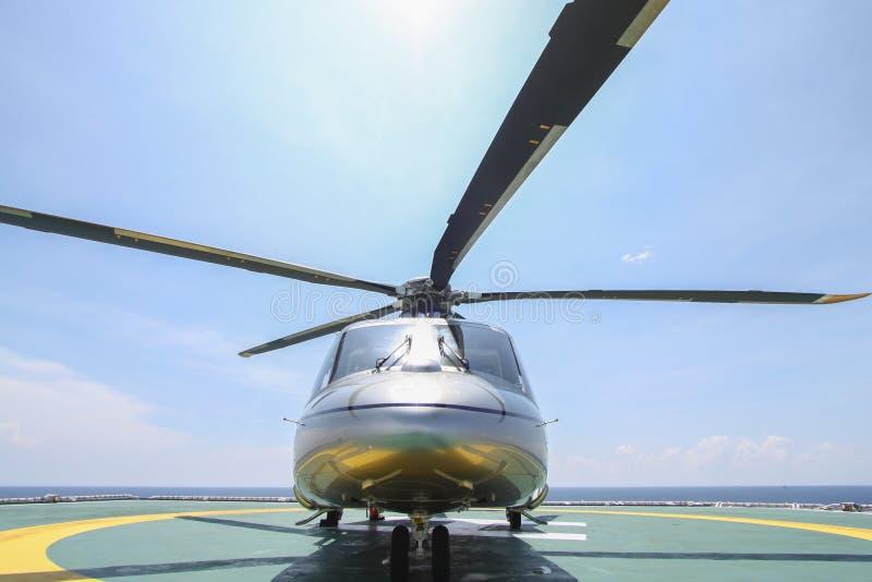 直升机在近海平台的停车处着陆 直升机调动乘员组或乘客工作的在近海油和煤气产业 库存图片