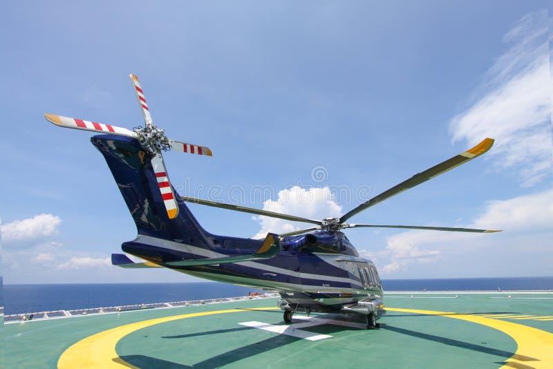 直升机在近海平台的停车处着陆 直升机调动乘员组或乘客工作的在近海油和煤气产业 免版税库存图片