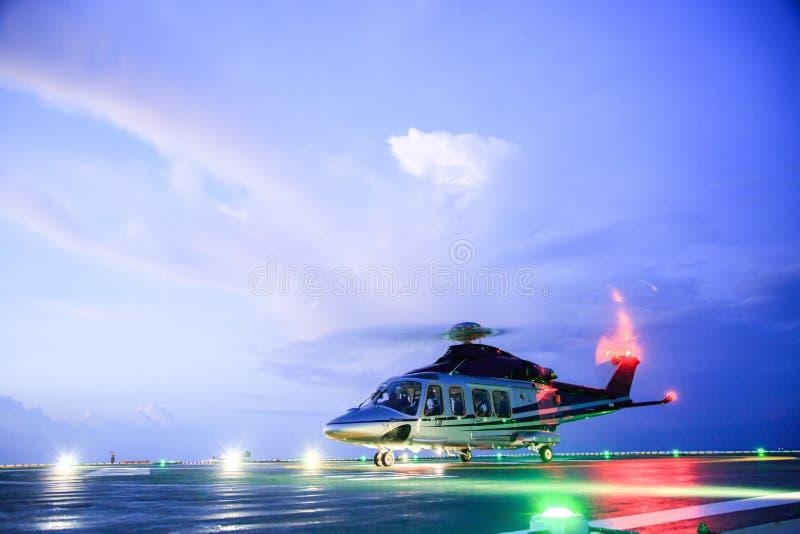 直升机在近海平台的停车处着陆 直升机调动乘员组或乘客工作的在近海油和煤气产业 免版税图库摄影