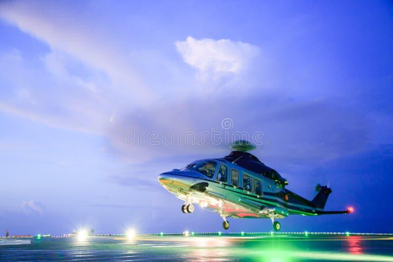 直升机在近海平台的停车处着陆 直升机调动乘员组或乘客工作的在近海油和煤气产业 免版税库存照片