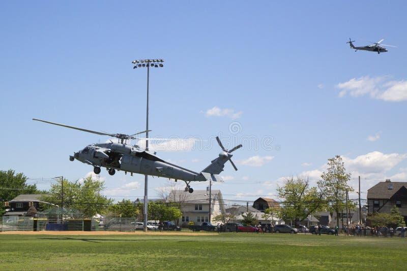 从直升机海的MH-60S直升机与与美国海军EOD队着陆的分谴舰队五交战水雷对抗措施示范的 图库摄影