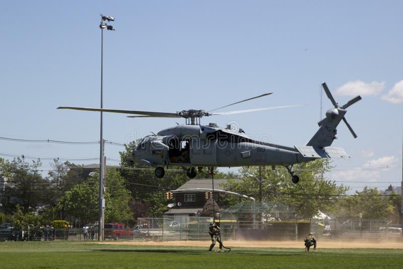 从直升机海的MH-60S直升机与与美国海军EOD队着陆的分谴舰队五交战水雷对抗措施示范的 库存图片