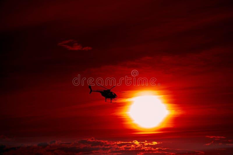 直升机飞行到日落里 免版税库存照片