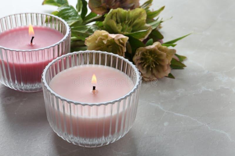 升蜡烛和鲜花在灰色大理石桌上 库存图片