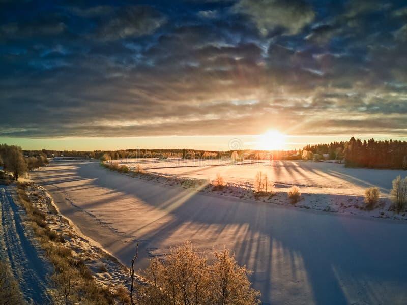 升起在冻河的太阳 免版税库存图片
