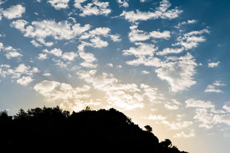 升起在地中海山土坎后的太阳的秋天风景 与云彩的蓝色和明亮的黄色天空 免版税库存图片
