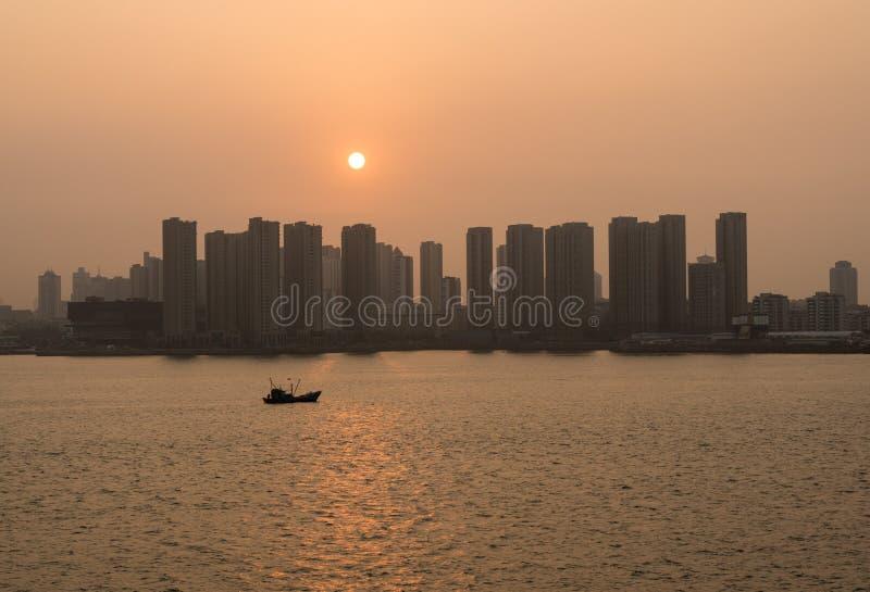 升起在青岛后高城市地平线的太阳在中国 库存图片