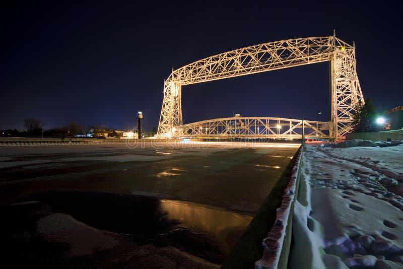 升降吊桥在德卢斯明尼苏达在晚上。在水的冰,冬天 库存图片