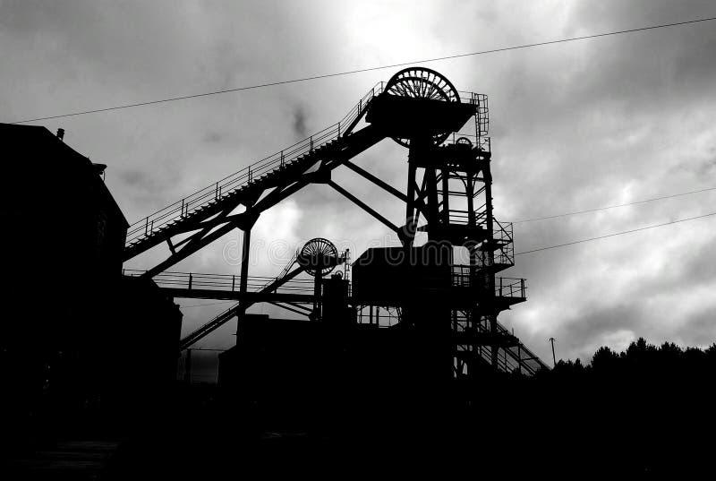 升降机构剪影在采矿井口的 免版税库存照片