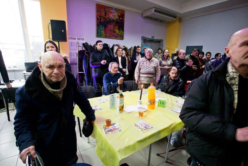 午餐前祈祷在无家可归者的圣诞节慈善晚餐的可怜的人民 图库摄影
