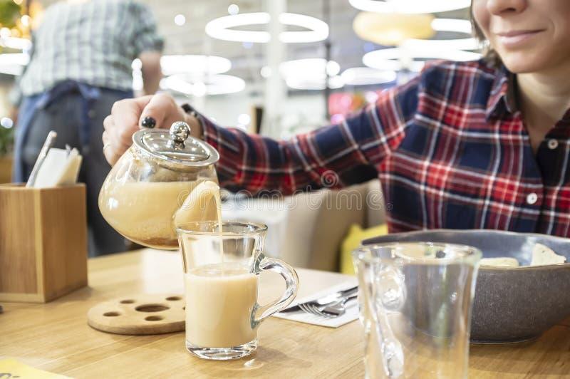 午餐在餐馆 妇女微笑预期印度masala饮料,她从一个玻璃茶壶倾吐入杯子, 库存图片
