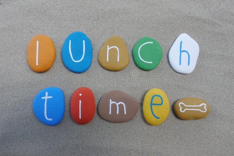 午餐时间,在海滩沙子的概念性多彩多姿的石头构成 免版税库存照片