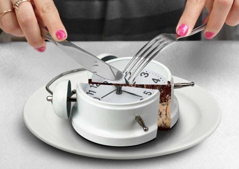 午餐时间概念,手切开了在板材的时钟 库存照片
