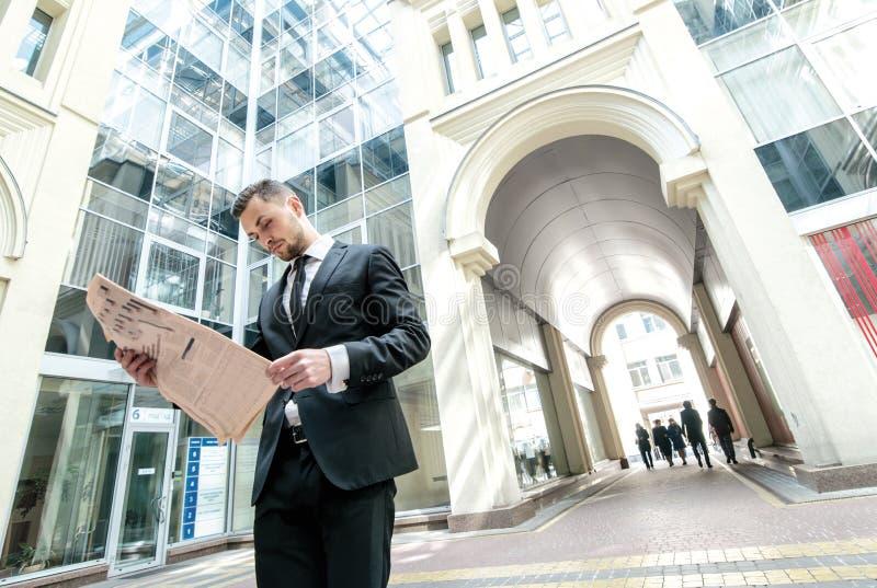 午餐的断裂 站立在街市r的商人礼服 免版税库存照片