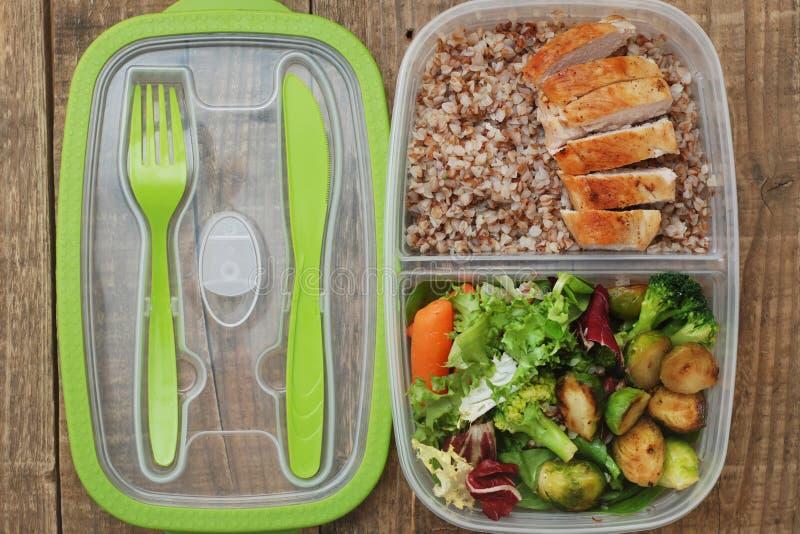 午餐盒健康食物拿走塑胶容器荞麦沙拉鸡肉布雷斯特土气木板 免版税库存照片