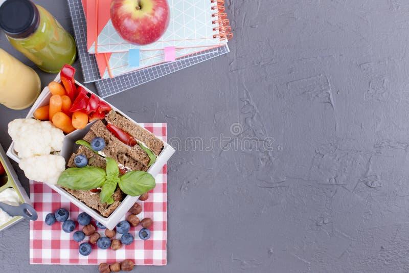 午餐盒用健康食物和汁液从新鲜的莓果 多士和苹果 学校和灰色背景的书 akeaway食物, 库存照片