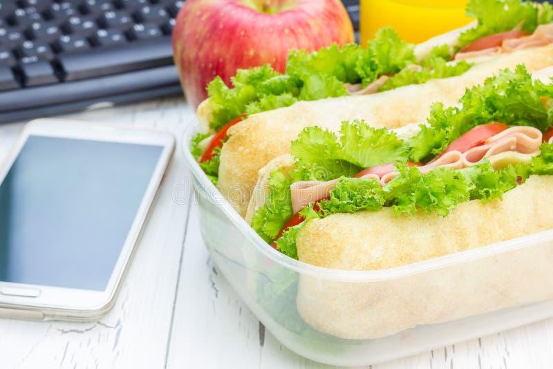 午餐盒用ciabatta面包三明治、苹果和橙汁 免版税库存图片