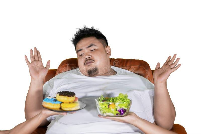 半信半疑的肥胖人选择沙拉或油炸圈饼在演播室 库存照片