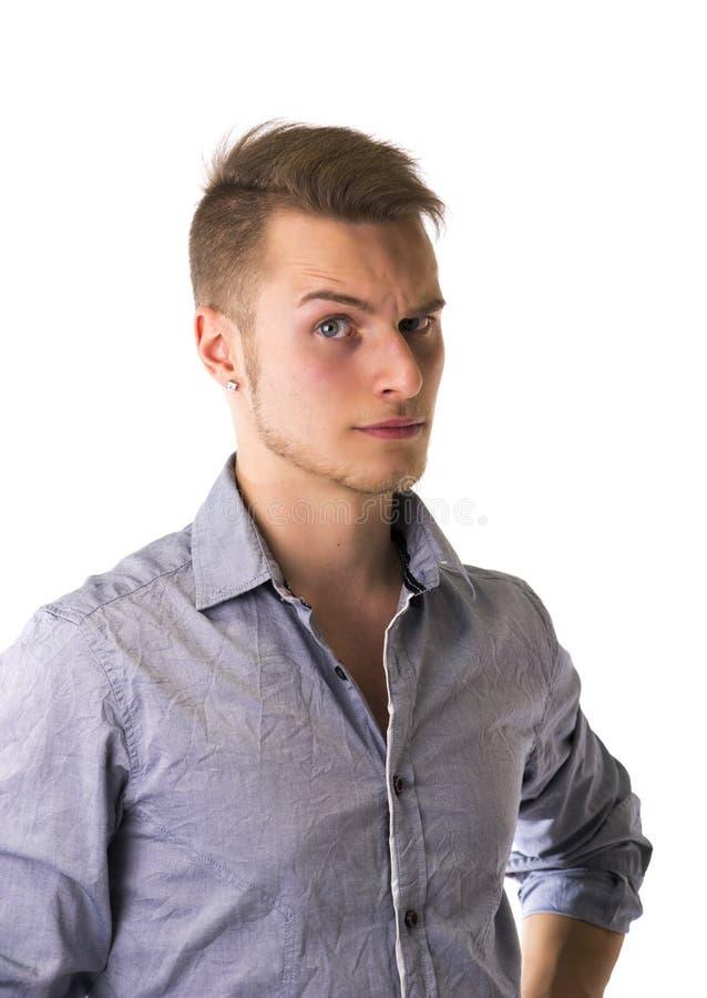 半信半疑,缺乏信心的英俊的白肤金发的年轻人 库存照片