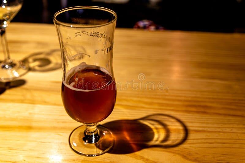 半在客栈木桌上的空的啤酒杯子 免版税库存照片