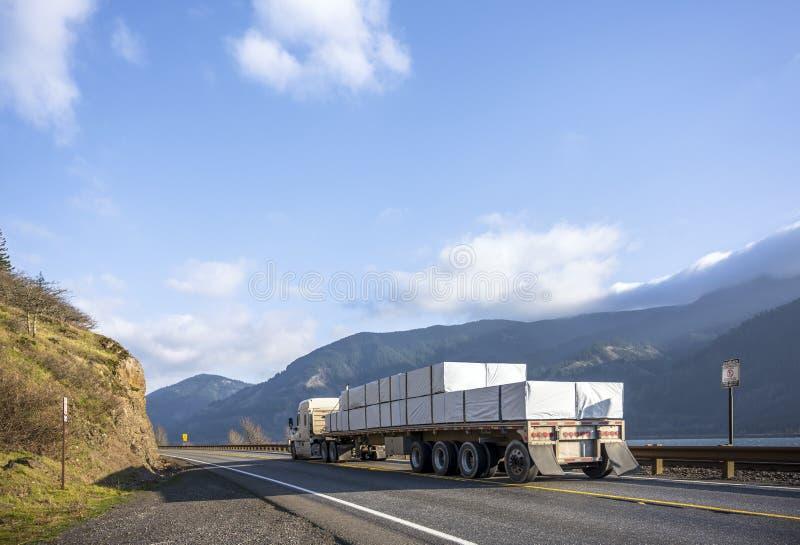 半大运输在平床半拖车的船具低小室卡车被盖的货物运行在路在哥伦比亚峡谷地区 图库摄影
